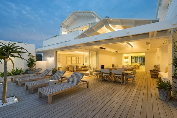 Pressure-treated wood luxury deck with modern home at twilight