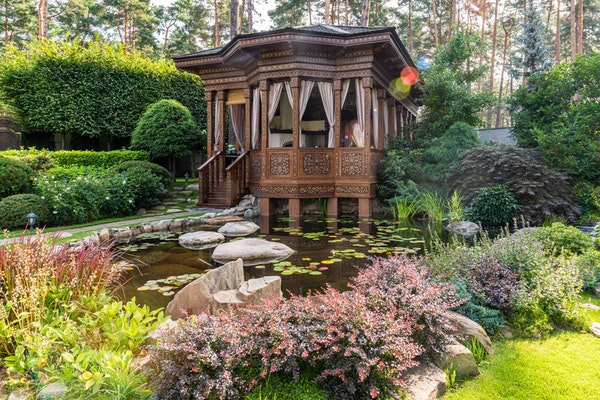 Asian gazebo-style deck with curtains overlooking pond with lilypads