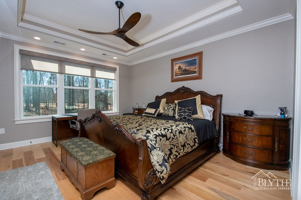 Master Bedroom With Wide Plank Hardwood Floors And Tray Ceiling 1