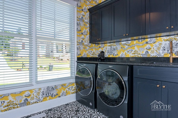 Luxury laundry room with black custom build-in cabinets, black counter, and black sink