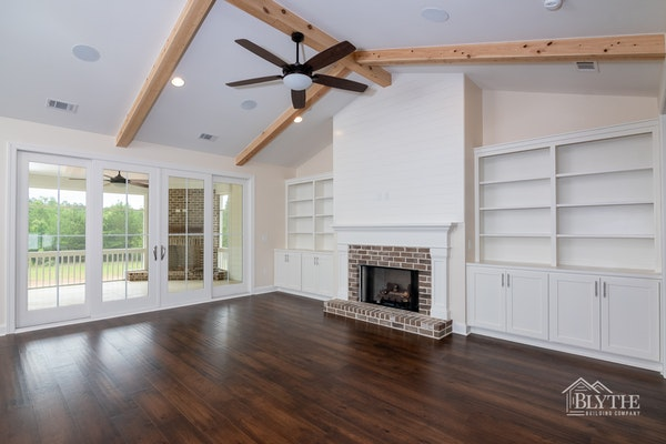 White mantle and legs with brick facing and brick hearth and shiplap fireplace wall and built-ins on each side of the fireplace