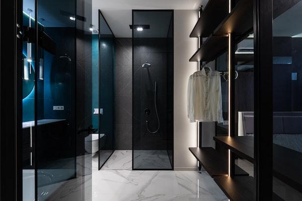 Black, modern, luxury walk-in closet with backlighting and modern bathroom