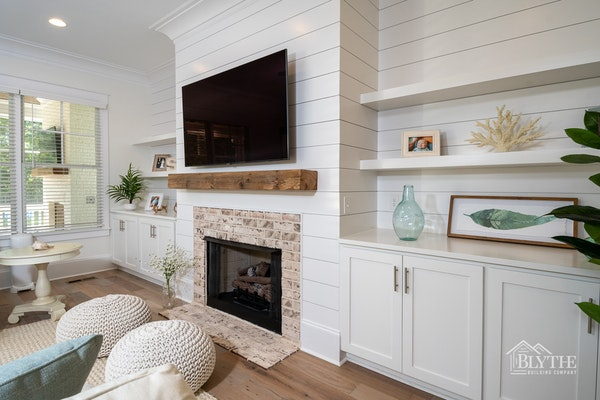 Fireplace with brick fireplace surround, rustic beam wood mantel, shiplap fireplace wall, and built-in bookcases