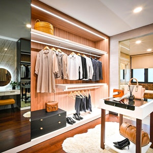 Luxury walk-in closet with contemporary mirror, vanity, and dressing table
