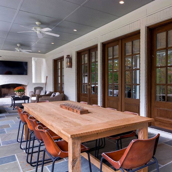 Outdoor dining room and living room with slate floor and masonry fireplace