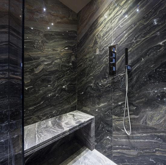 dark marble shower with dramatic veining